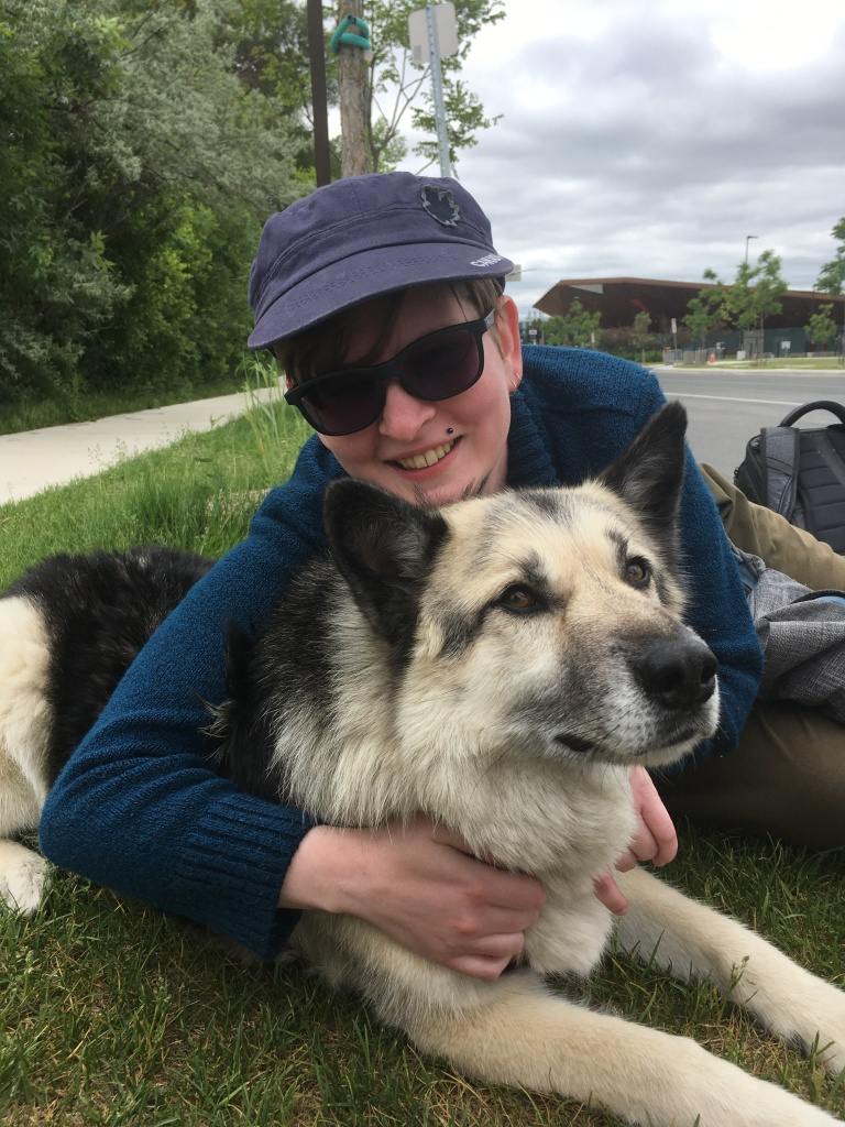Image description: My smiling wearing a blue hat ,sweater and sunglasses/ I'm smiling while cuddling a husky. Strike dogs made the strike more bearable