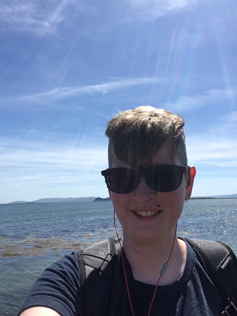 Image description: Me in Ireland My hair is also on vacation and is trying to get to know my glasses better by being shoved forward in a blond triangle
