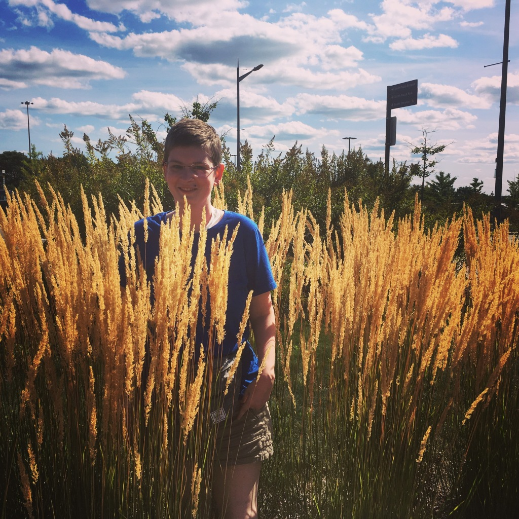 Image Description: A white woman stands in tall grass