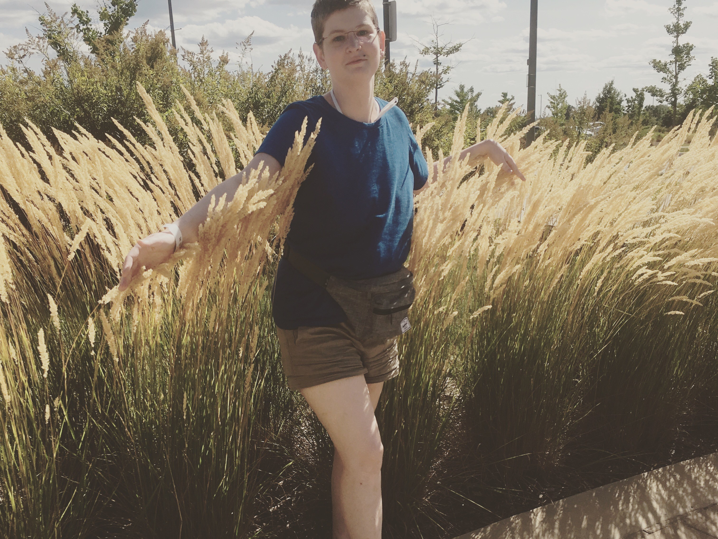 Image description: A blond white woman wearing a blue, shirt,beige shorts and a fanny pack, walks out of some tall grass arms outstretched
