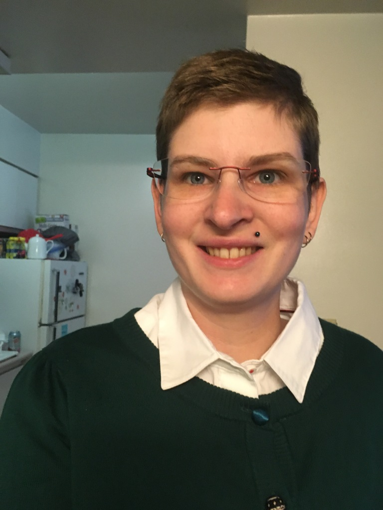 Image Description: A white woman with blond hair and glasses is smiling at the camera while wearing a white button down oxford shirt under a green cardigan