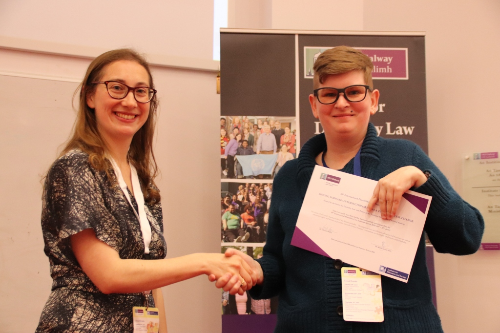 Image Description: Me shaking hands with a smiling woman with light brown hair. I am holding the certificate in my left hand