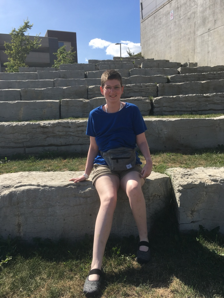 Photo of me a white woman with left side cerebral palsy. I am wearing a blue shirt beige shorts and a fanny pack. I am sitting on stone seating surrounded by grass