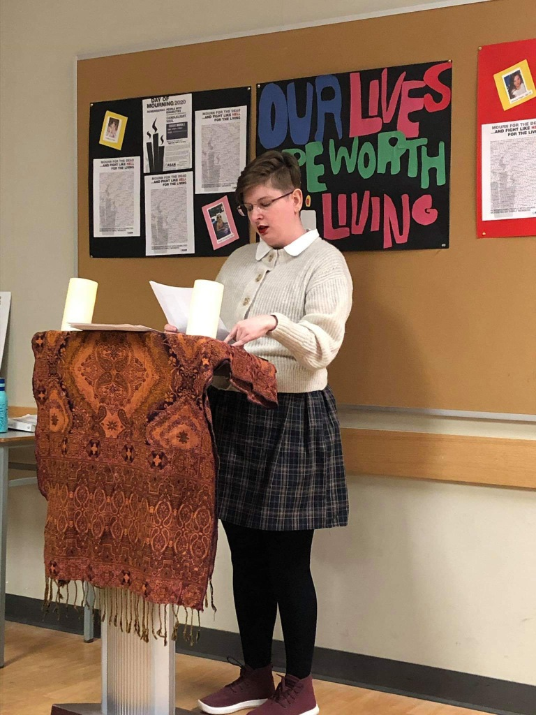 Image Description: Me, a pale blonde woman wearing a plaid dress and cream coloured sweater standing at a podium, reading names off of a list for the Disability Day of Mourning