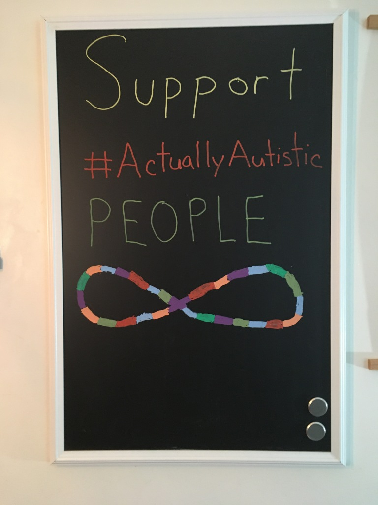 "Image Description: Photo of a blackboard that says ""Support #ActuallyAutistic People"" with a multicoloured infinity symbol at the bottom"