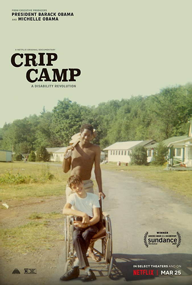 Image Description: Poster for the Netflix Documentary Crip Camp. The Title is in white in the upper left corner. In the background are  white buildings in the foreground a shirtless black man leans a guitar over his right shoulder while pushing a white young man wearing trousers and a white shirt in his wheelchair