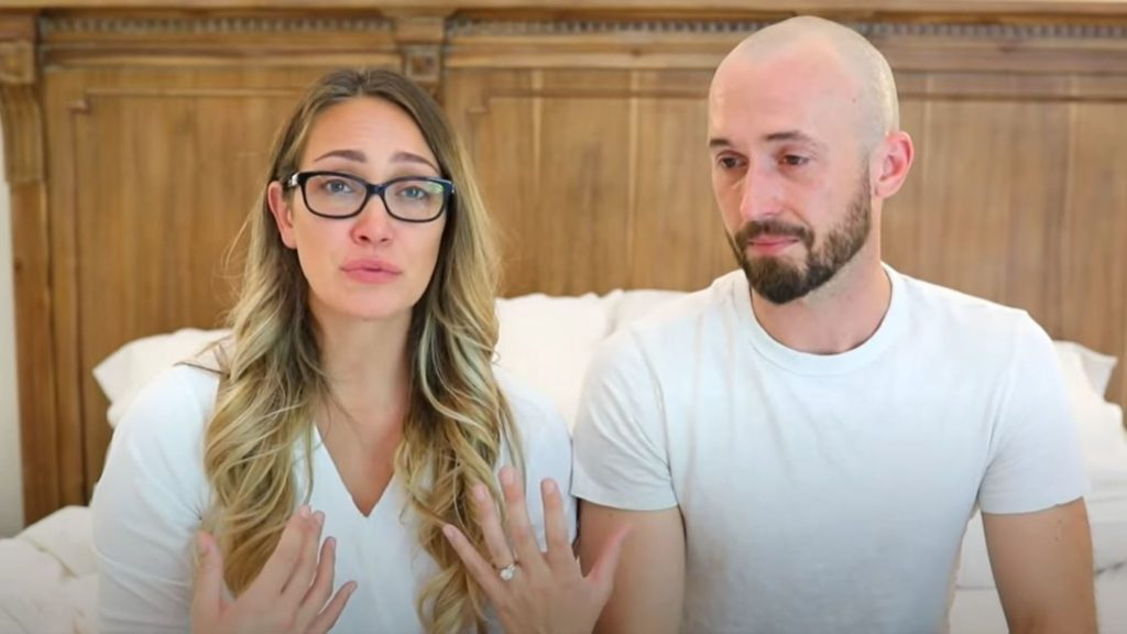 Image description: A white couple Myka and James Stauffer sit on a white bed while both wearing white shirts. Myka has dyed blonde hair and is wearing glasses, James has a beard and is bald
